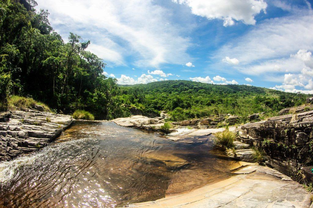 Uma pequena margem de uma cachoeira. Ao fundo, um céu azul repleto de nuvens e uma zona verde em árvores imensa.