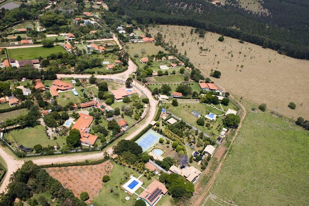 Uma vista aérea e panorâmica da cidade da Cabreúva. Nela há casas dispersas e à direita uma reserva verde, repleta de árvores.