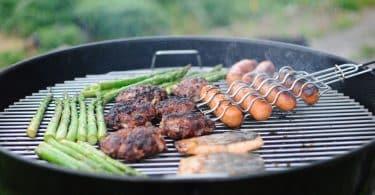 Linguiças e carne: um churrasco sendo feita numa churrasqueira.