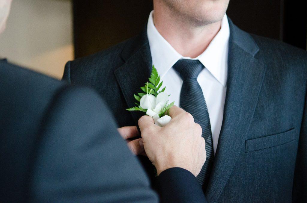 Ao fundo, um homem de terno. Em primeiro plano, embora situado com desfoque, vê-se um homem colocando um ramo de pequenas plantas sobre o terno do outro homem.