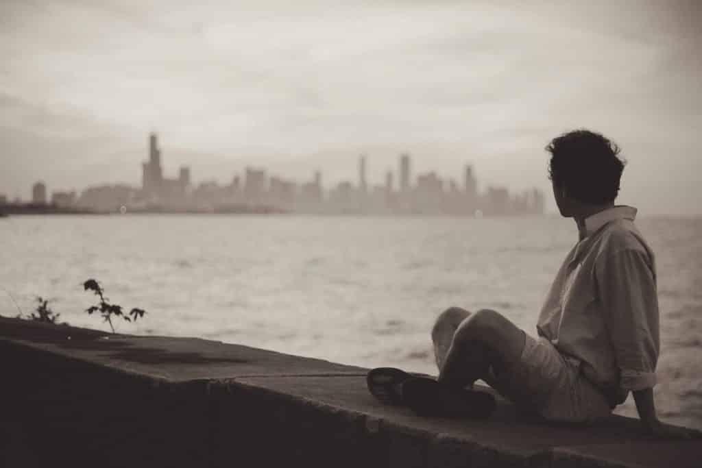 Um homem contemplando, a distância, uma zona urbana grande/uma cidade. Dividindo ambos, um grande rio.