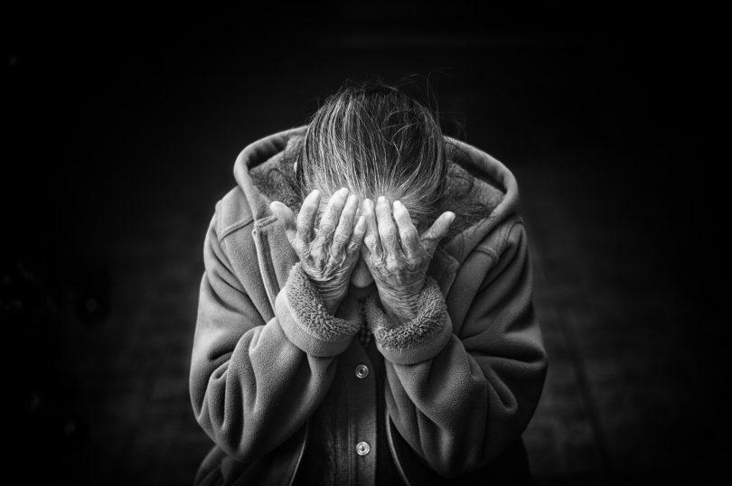 Uma mulher idosa colocando as mãos sobre o rosto