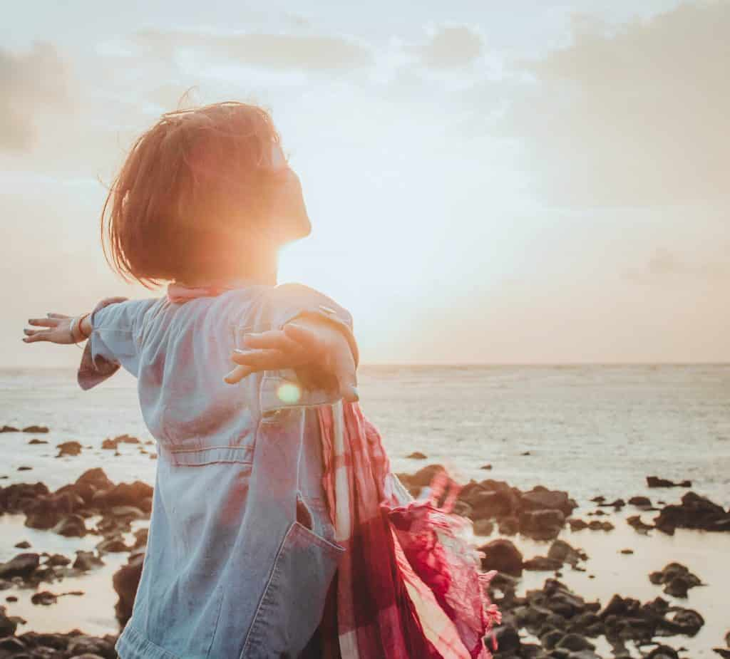 Uma mulher de braços erguidos contemplando um pôr-do-sol no mar.