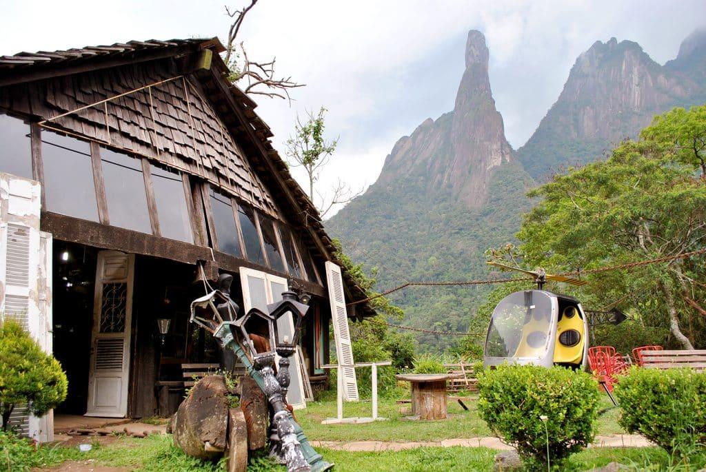 Local conhecido como Parque Nacional da Serra dos Órgãos. Ao fundo, uma região montanhosa, com cumes altos. Embaixo, um jardim com um helicóptero e uma casa.