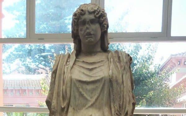 Uma estátua antiga de Deméter com rupturas e quebraduras. A estatua não tem o nariz de Deméter, supostamente quebrado ou destruído.