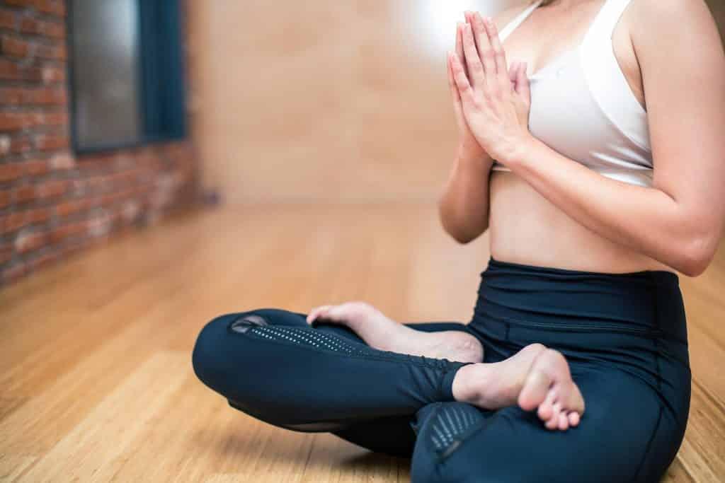 Uma mulher de blusa branca e calças leggings preta fazendo yoga.