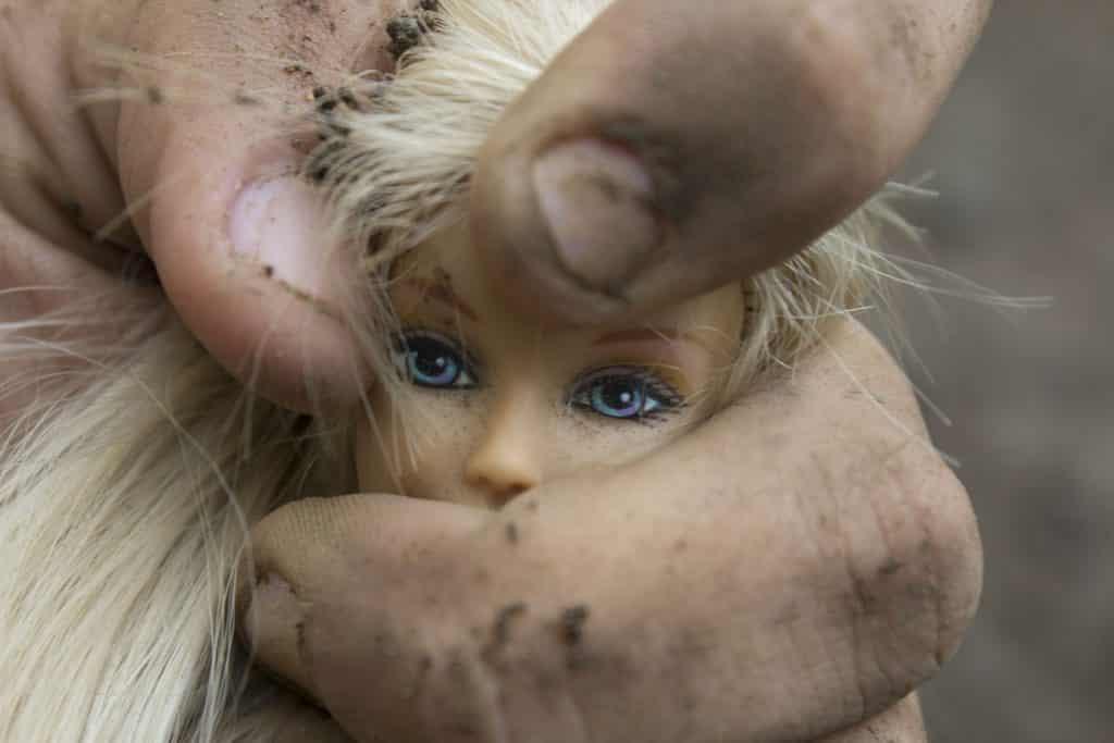 A cabeça de uma boneca feminina sendo apertada por uma mão possivelmente masculina.