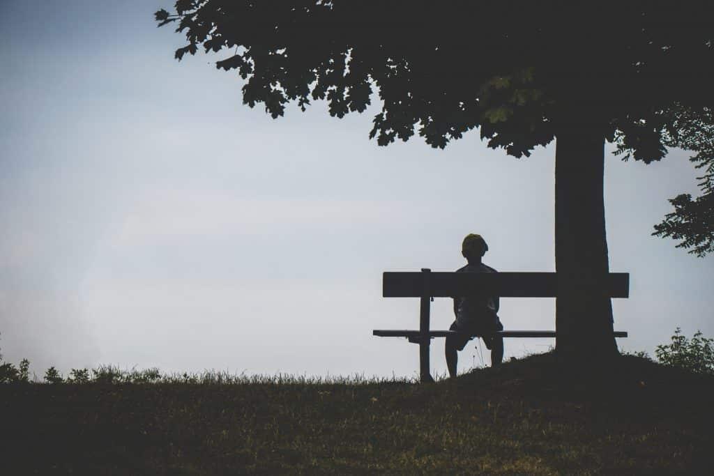 Uma pessoa isolada sentada num banco, vista por trás. Ao lado dela, uma árvore.