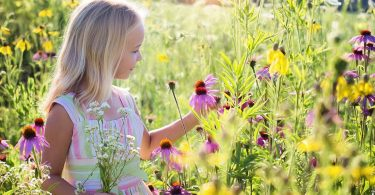 Uma garota branca de cabelos loiros em meio a um campo florido. Ela segura uma flor
