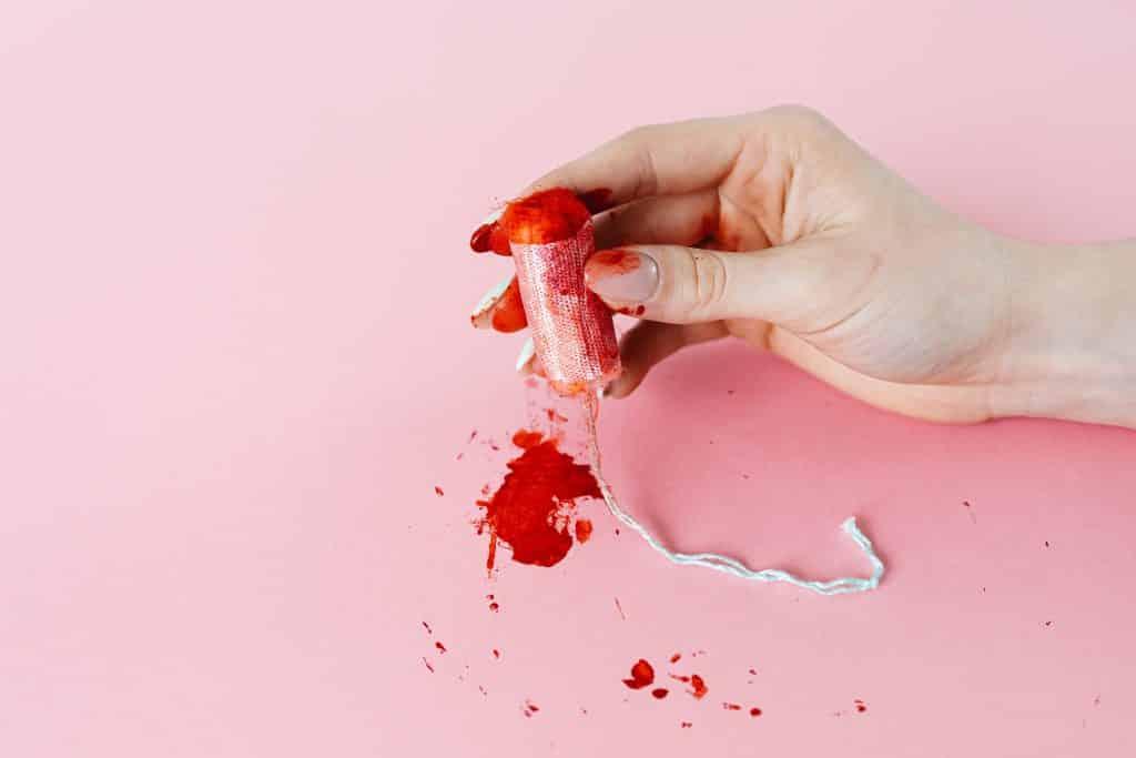 Uma mão feminina manchada de tinta vermelha. No fundo, sobre um plano rosa, manchas de tinta vermelha.