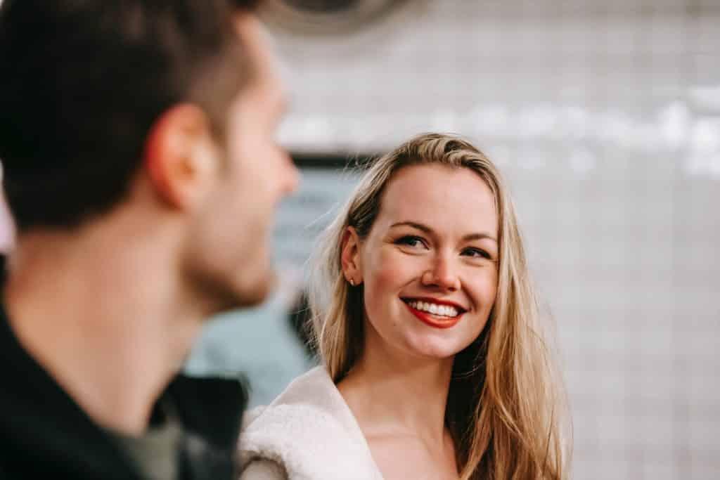 Uma mulher branca sorrindo e olhando para um homem branco.