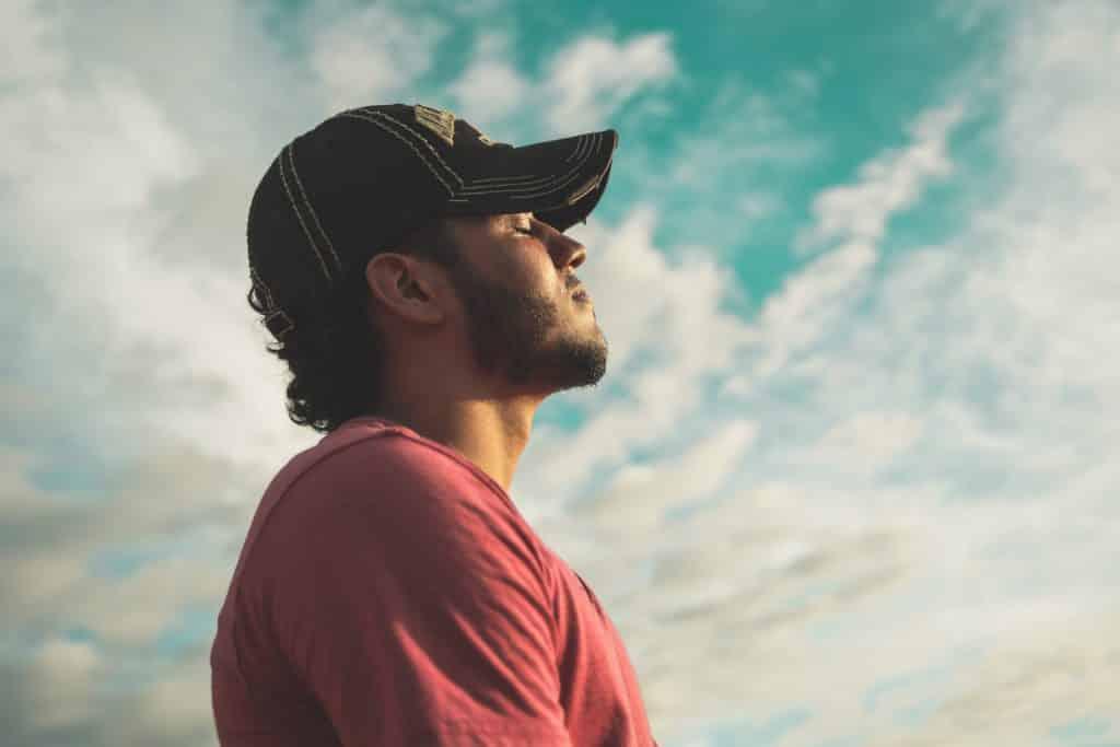 Um homem de boné preto e camiseta vermelha com o rosto fazendo frente ao sol. Ele parece suspirar.