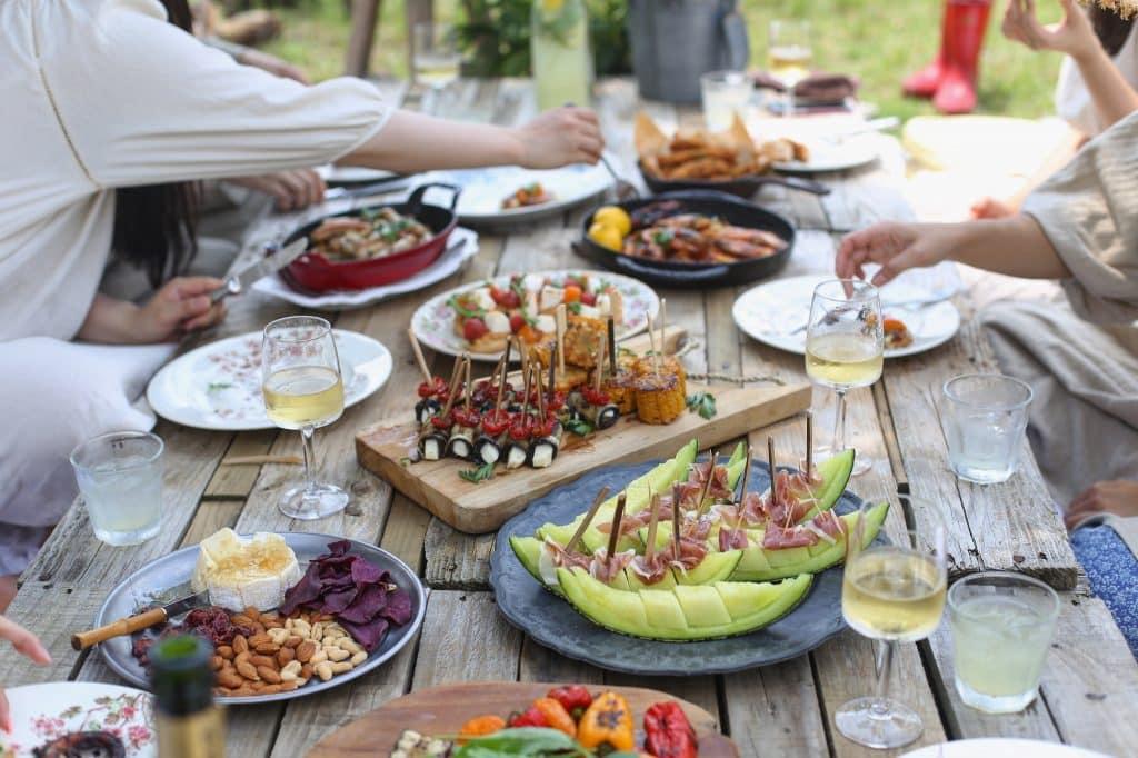 Pessoas sentadas à mesa fazendo um churrasco.
