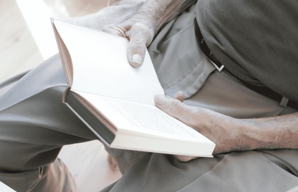 Duas mãos de um idoso segurando um livro aberto.