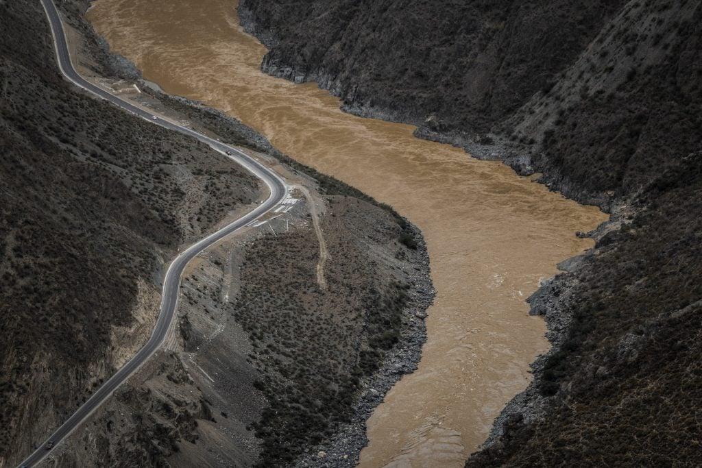 Um extenso rio poluído visto de cima, À esquerda, uma estrada.