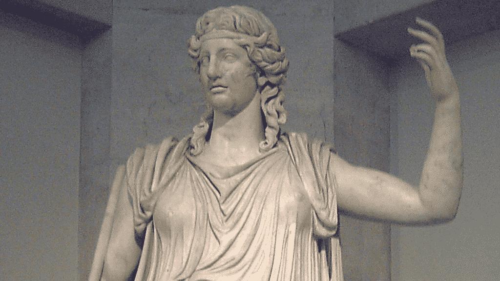 Uma estátua que representa a deusa Deméter. Ela está com o braço esquerdo erguido.