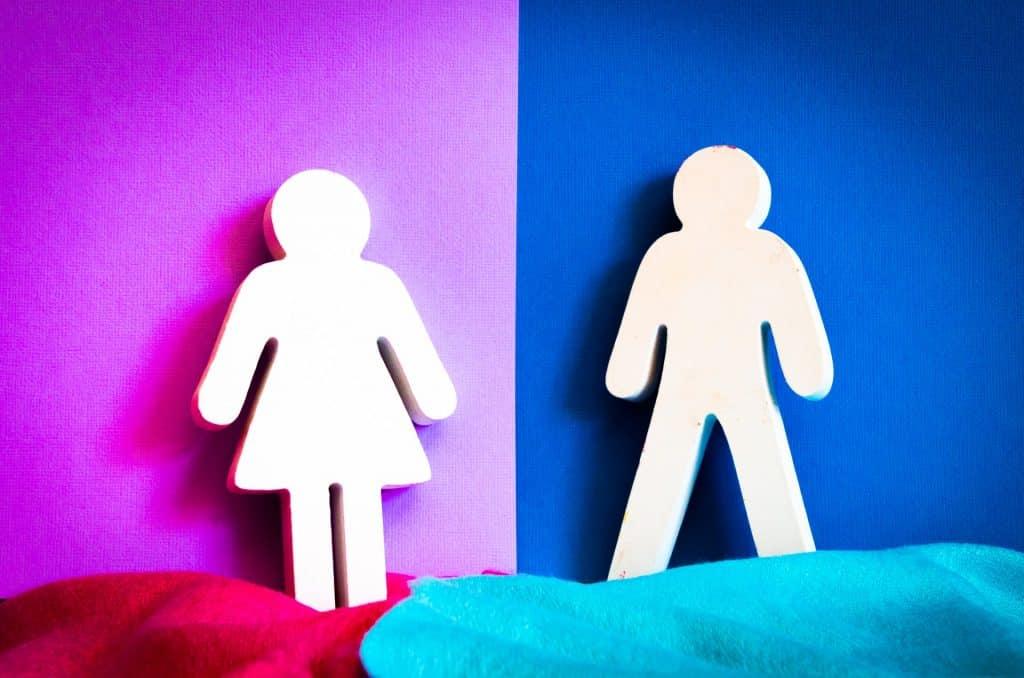 Um boneco que sinaliza o sexo feminino e, à direita, um que simboliza o sexo masculino.