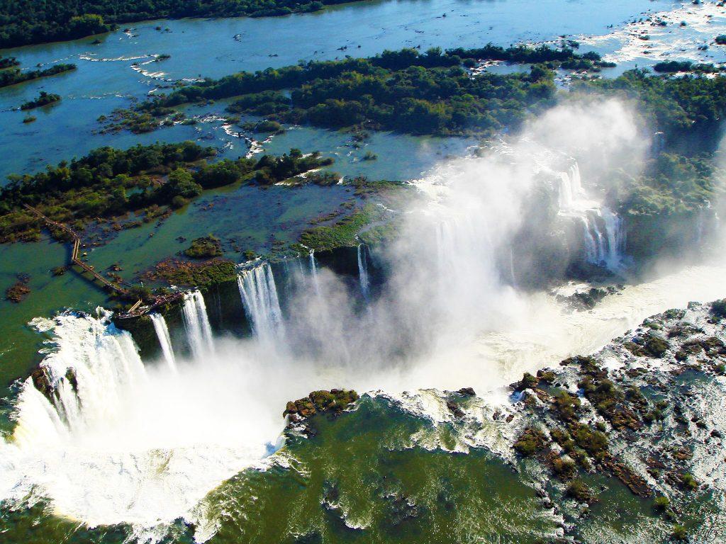 Uma visão aérea das passarelas aquáticas e das cataratas de Foz do Iguaçu. Grandes cachoeiras e, acima delas, zonas esverdeadas com águas rasas.