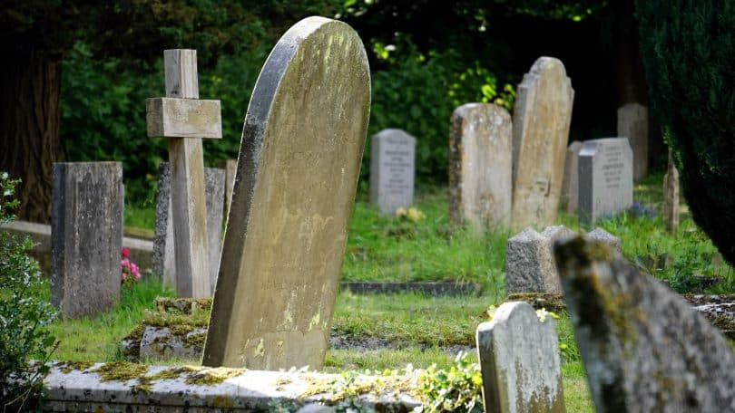 Várias lápides dispostas em um gramado de cemitério.