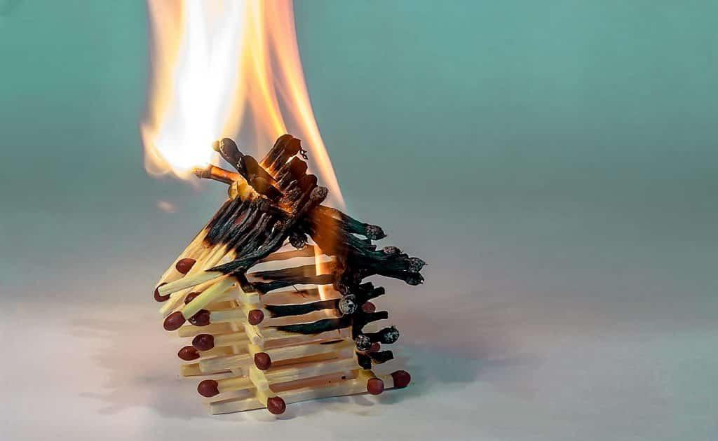 Uma miniatura de casa composta por fósforos. Eles estão sendo queimados.