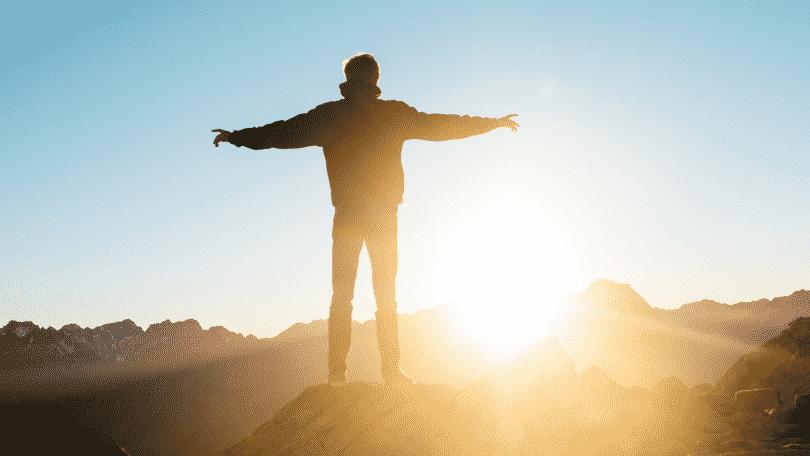 Um homem de braços erguidos em frente ao pôr-do-sol/nascer do sol.