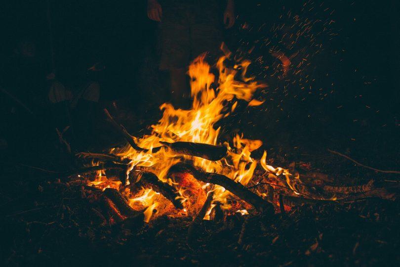 Uma fogueira sendo realizada no escuro.