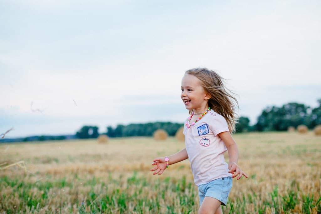 Uma garotinha sorridente correndo num vasto campo verde.