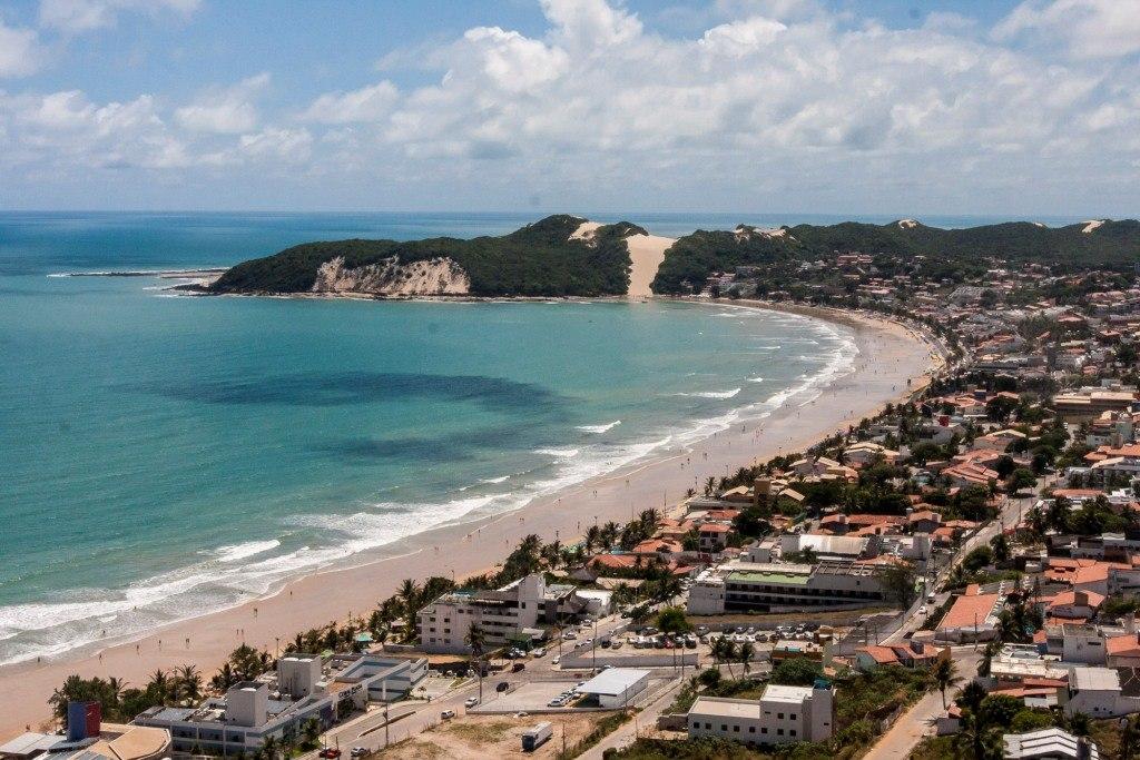 Uma praia com litoral vasto e curvilíneo. À direita, várias casas e estabelecimentos. Ao fundo, o mar e uma zona verde com árvores e areia.