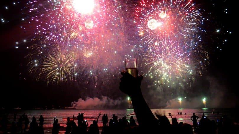 Fogos de artifício luminosos em meio à escuridão. Embaixo deles e em primeiro plano, pessoas de braços erguidos e comemorando.