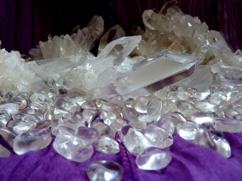 Fragmentos, gemas e pedaços de quartzo transparentes debruçados sobre um manto roxo.