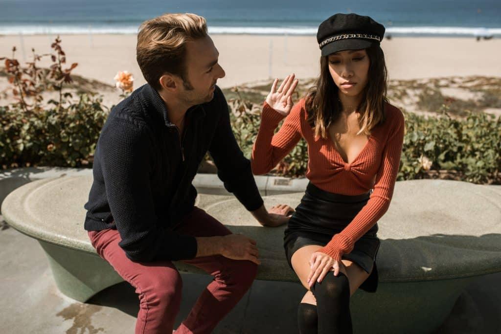 Um homem branco, à esquerda, olhando para uma mulher asiática. A mulher ergue a mão direita. Ambos estão sentados em um banco.