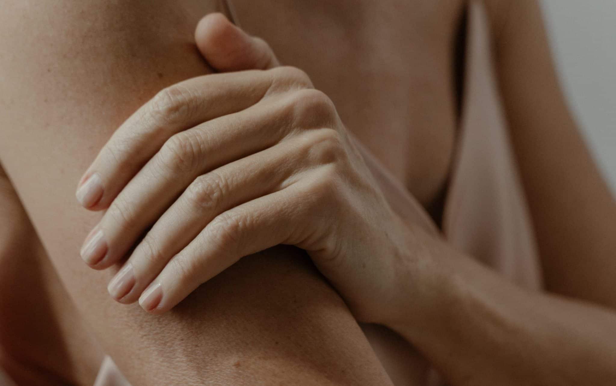 Uma mulher colocando sua mão esquerda sobre seu braço direito. Sua pele tem um aspecto envelhecido.