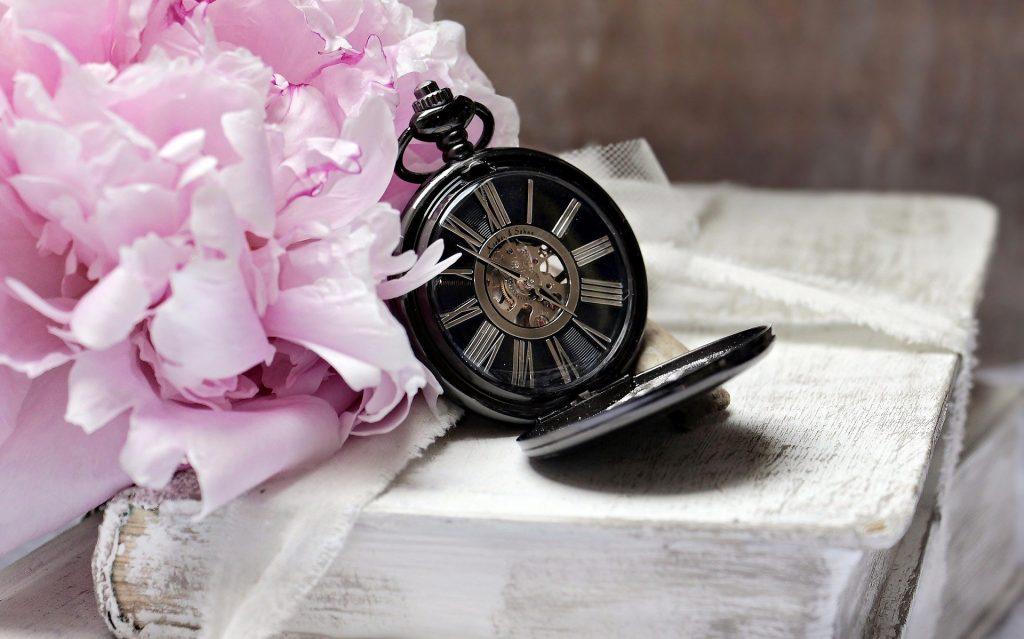 Flores rosas à esquerda e, ao lado, um relógio manual romano. Em baixo de ambos, um livro fechado.