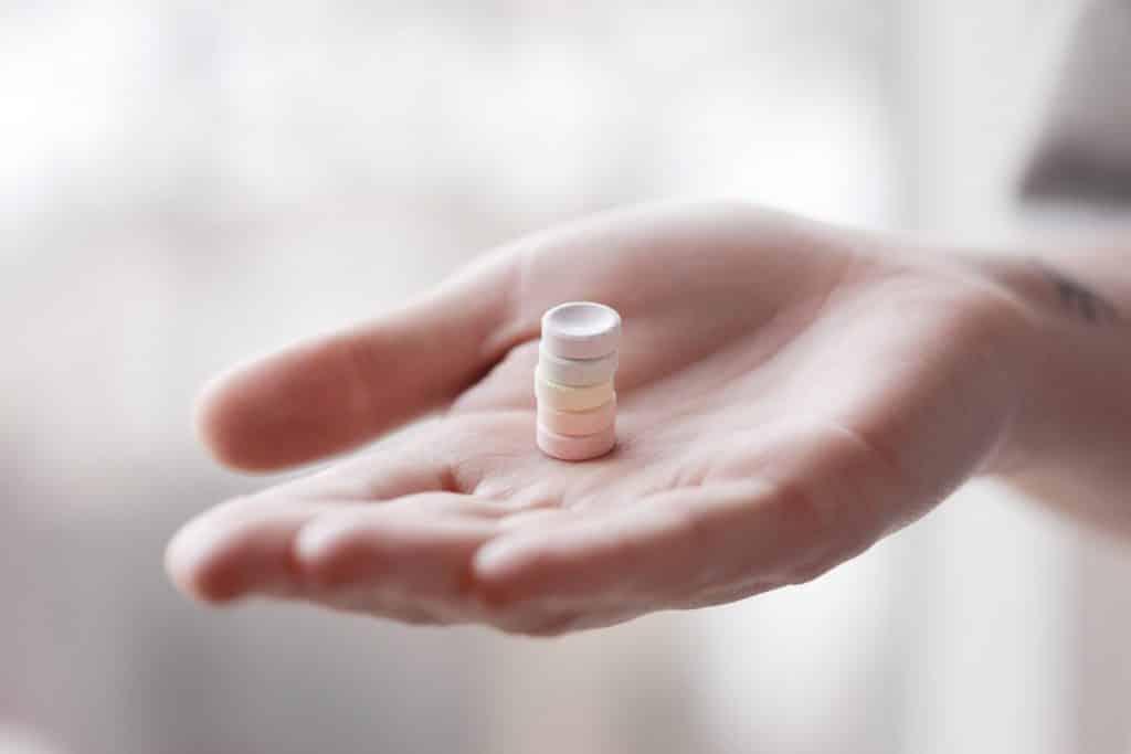 Uma mão estendida com cinco pequenos comprimidos sobre sua palma.