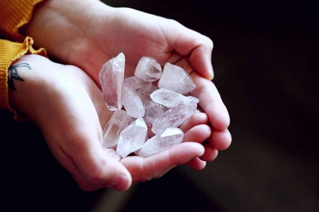 Duas mãos em concha segurando pedaços de quartzo transparente.