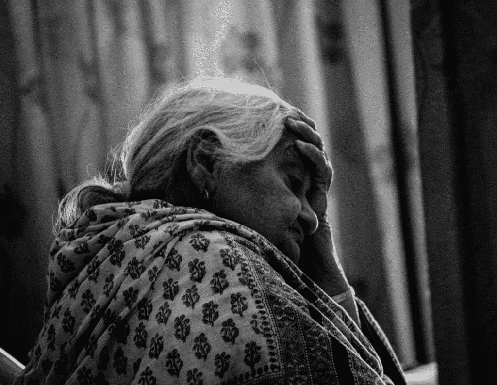 Uma mulher idosa com a mão sobre a testa e olhando pra baixo.