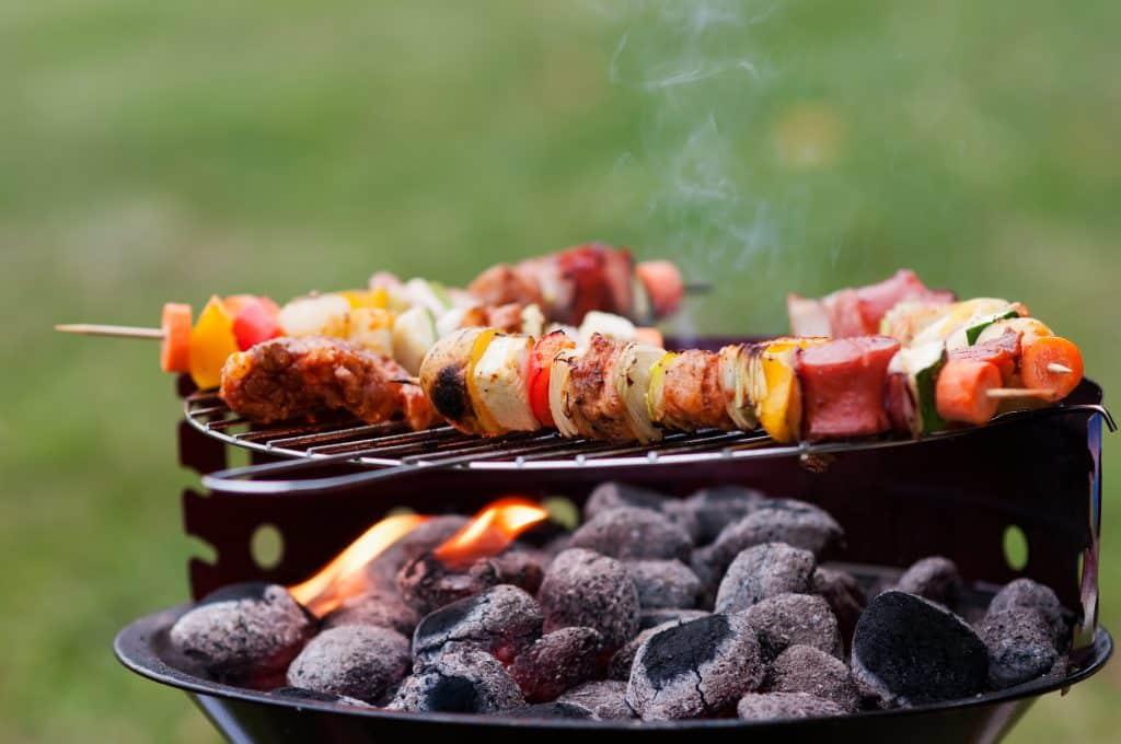 Espetos de carnes e alimentos variados sendo feitos em uma churrasqueira. Embaixo dos espetos, subjazendo a uma grade, carvão.