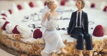 Sobre um bolo, miniaturas de noivos, sendo uma representante de um homem e a outra de uma mulher.