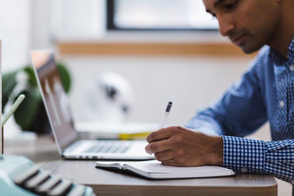 Um homem escrevendo sobre um caderno posto numa mesa. Nessa mesa, desfocado, um notebook.