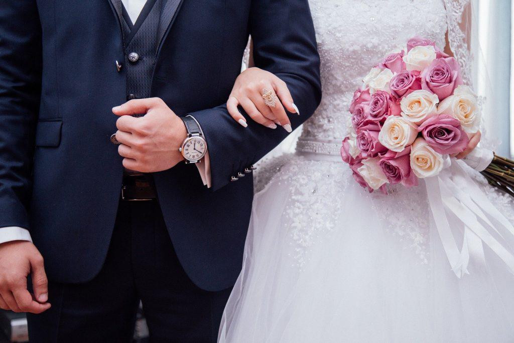 Um homem trajado de terna e, à sua esquerda, uma mulher vestindo um vestido e segurando um buquê de flores. A mão esquerda da mulher está sobre o braço esquerdo do homem.