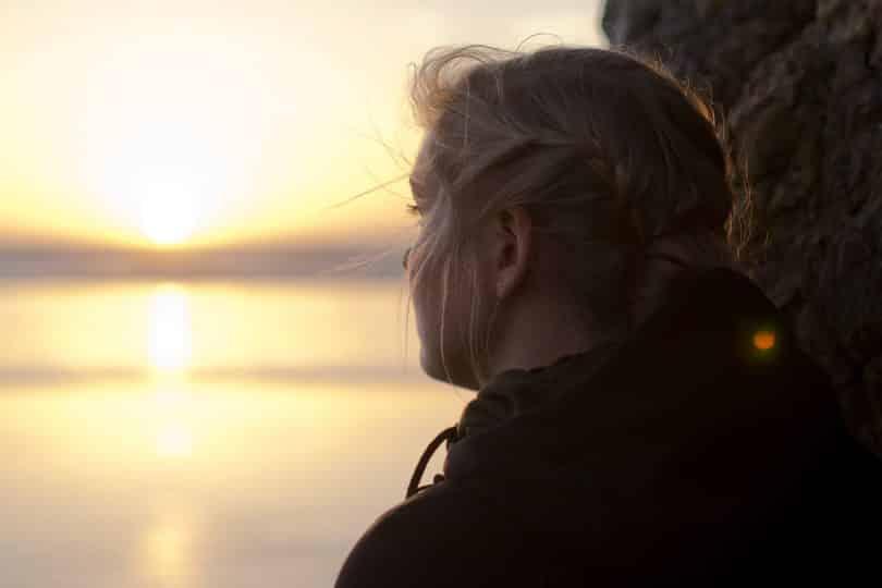 Uma mulher loira contemplando uma forte luz solar.