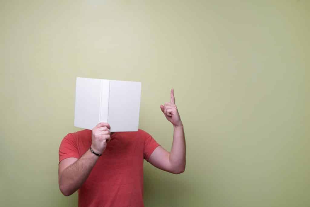 Um homem lendo um livro branco e com o dedo indicador esquerdo erguido.