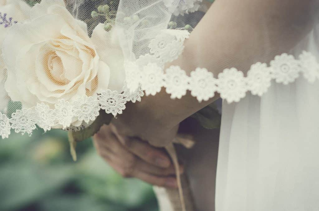 Braços e mãos supostamente femininas segurando um buquê de flores. Sobre os braços, um véu branco caindo sutilmente.