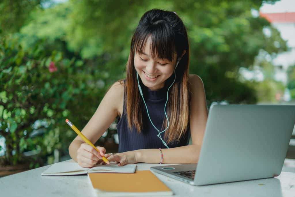 Uma mulher asiática fazendo anotações em um caderno. Em sua mesa, outro caderno e um notebook. Ela sorri e usa fones de ouvido.