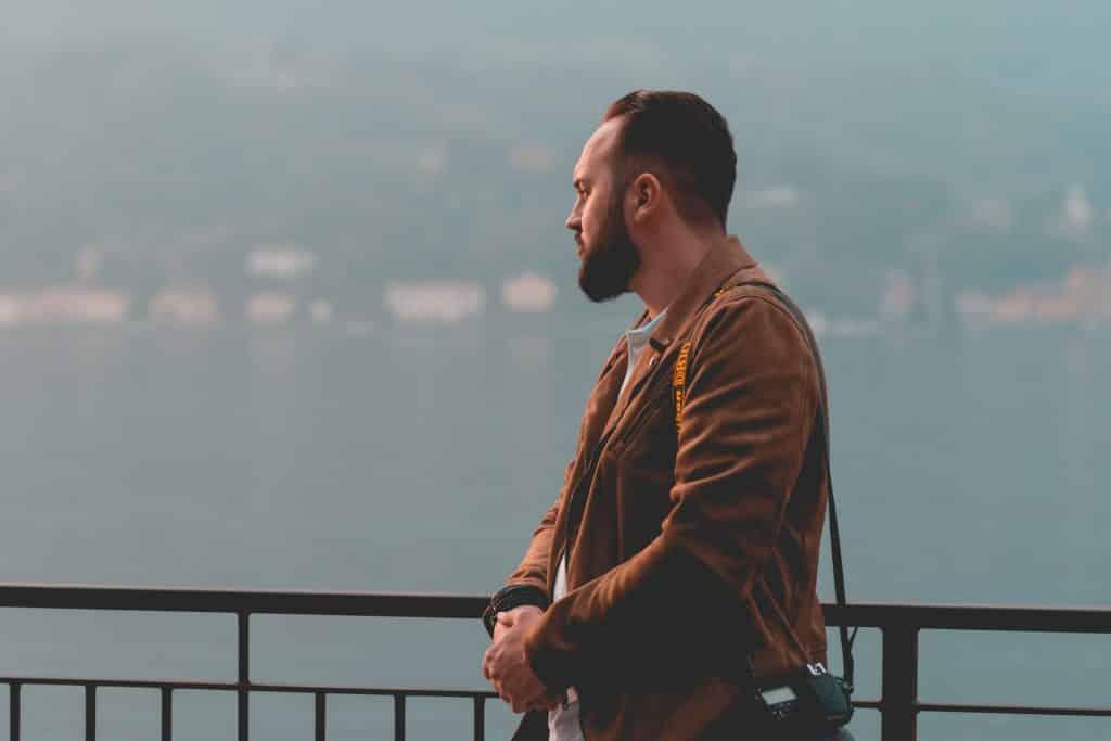 Homem branco olhando para horizonte.