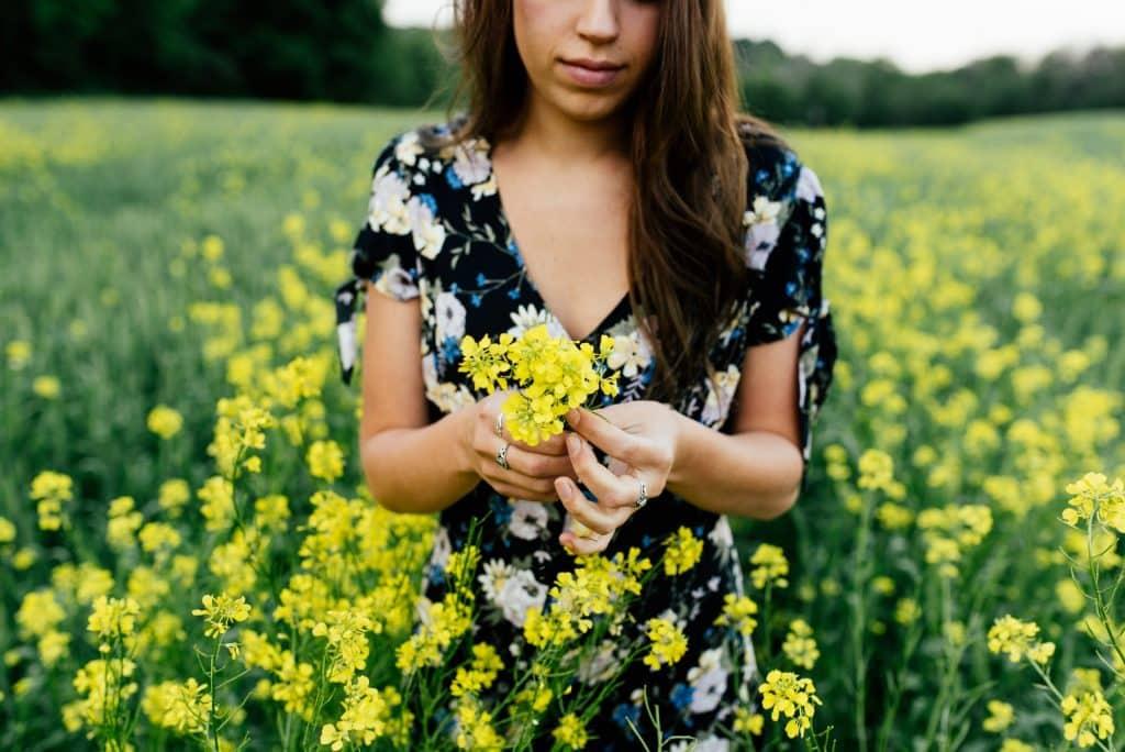 Mulher branca com flores amarelas.