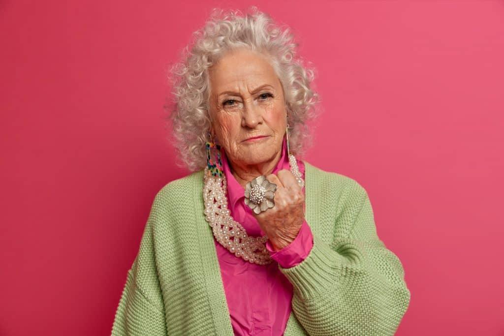 Uma mulher madura, de cabelos fazendo um punho erguido/e ou cerrado com a mão, demonstrando raiva.
