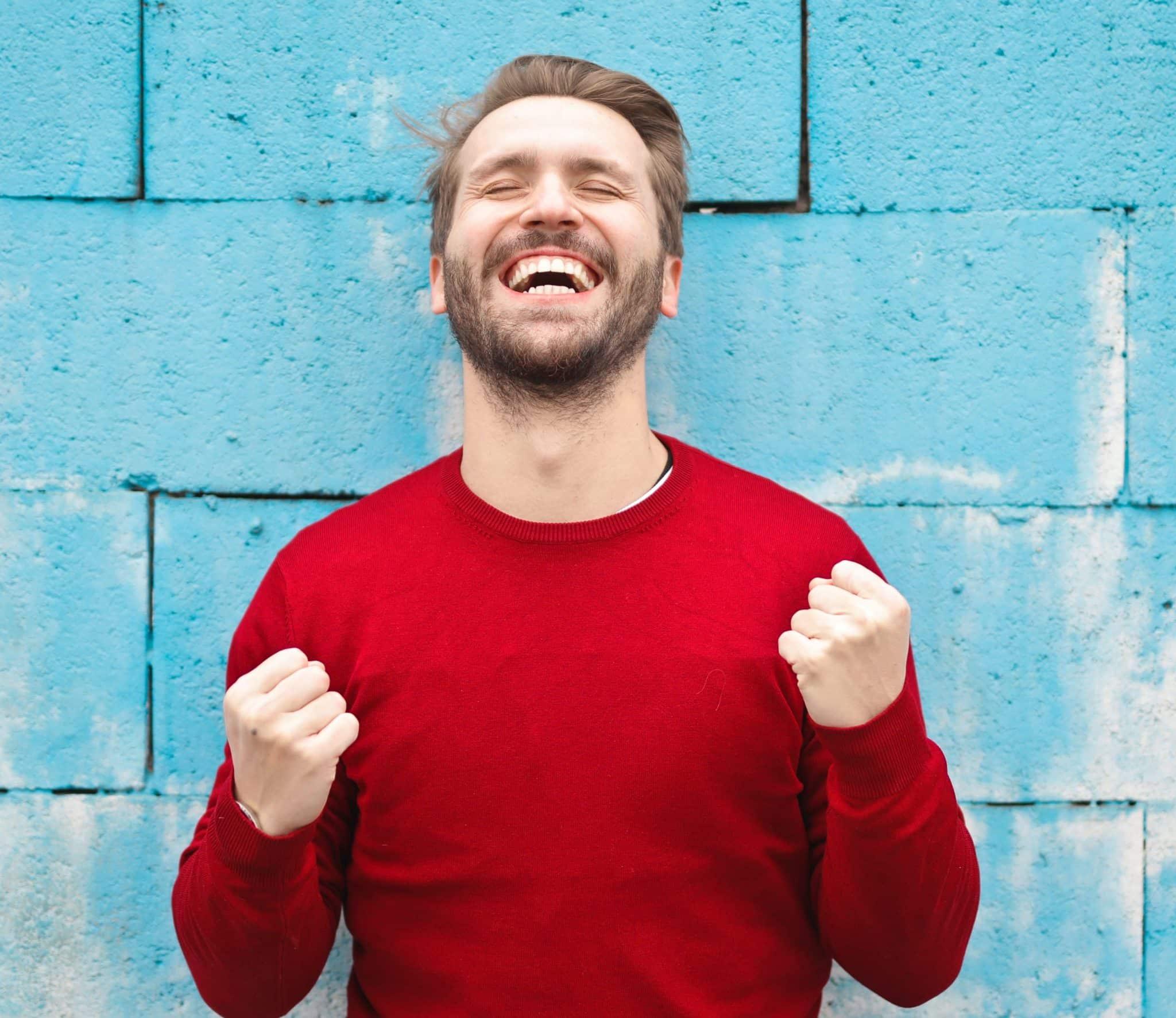 Um homem branco e de blusa vermelha. Ele olha pro alto e sorri, também com os punhos levemente erguidos.