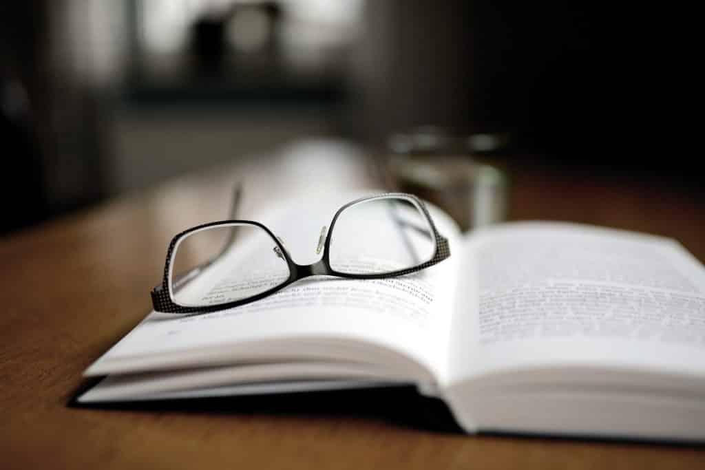 Um livro aberto com um óculos de armação preta em cima dele.