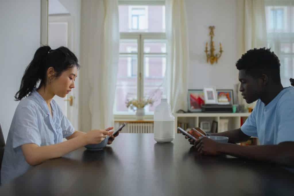 Uma mulher e um homem situados à mesa, cada um, usando um celular